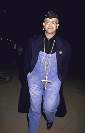 Elton wearing overalls and a large cross necklace in 1991.