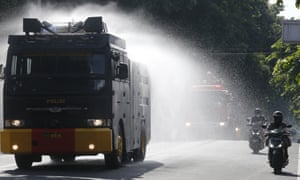 An Indonesian police water cannon vehicle sprays disinfectants at public road amid fears of the new coronavirus outbreak in Bali, Indonesia on Tuesday, 31 March, 2020.