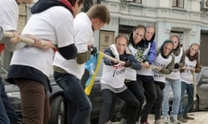 Activists, some wearing Putin masks, stage a tug of war in front of the Dutch embassy in Kiev to urge the Netherlands to vote yes to the association treaty with Ukraine