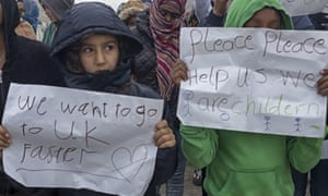 Children hold placards requesting UK assistance during the dismantling of the Calais refugee camp.