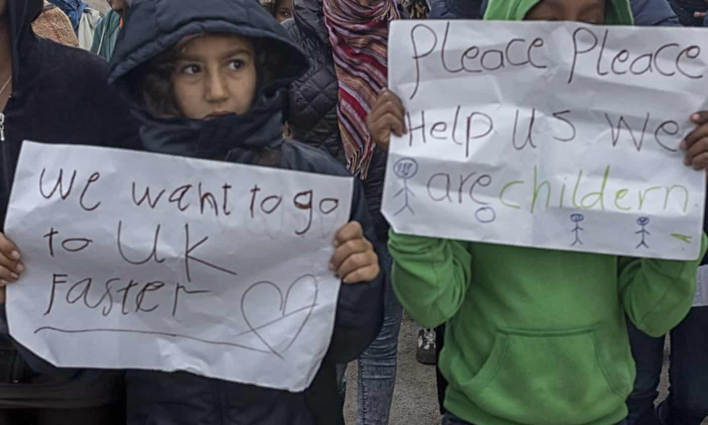 Children at the Calais refugee camp hold up handwritten signs, asking for help