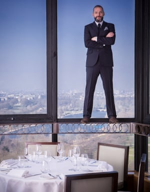 Fred Sirieix standing in the window of his restaurant wearing a suit