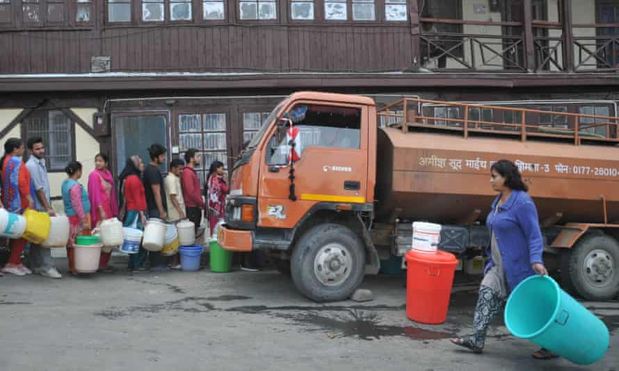 People queue to collect drinking water in buckets from a truck in Shimla.