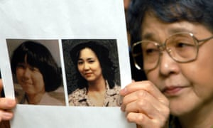 Megumi Yokota's mother with pictures of the girl who was abducted when she was 13