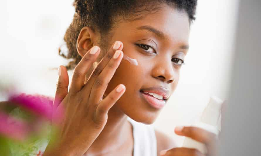 A woman putting on face lotion.