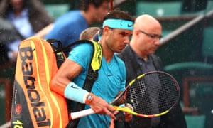 Rafa Nadal heads off court as rain interrupts his quarter-final against Diego Schwartzman.