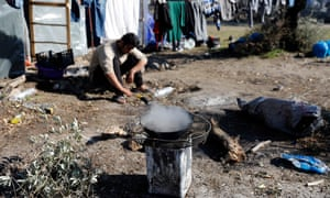A migrant from Afghanistan cooks on a makeshift stove.