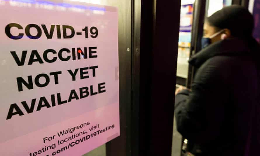 A person walks past sign informing customers about Covid-19 vaccine availability at a drug store in New York this week.