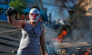 A masked demonstrator at a burning barricade during protests in Valparaiso, Chile