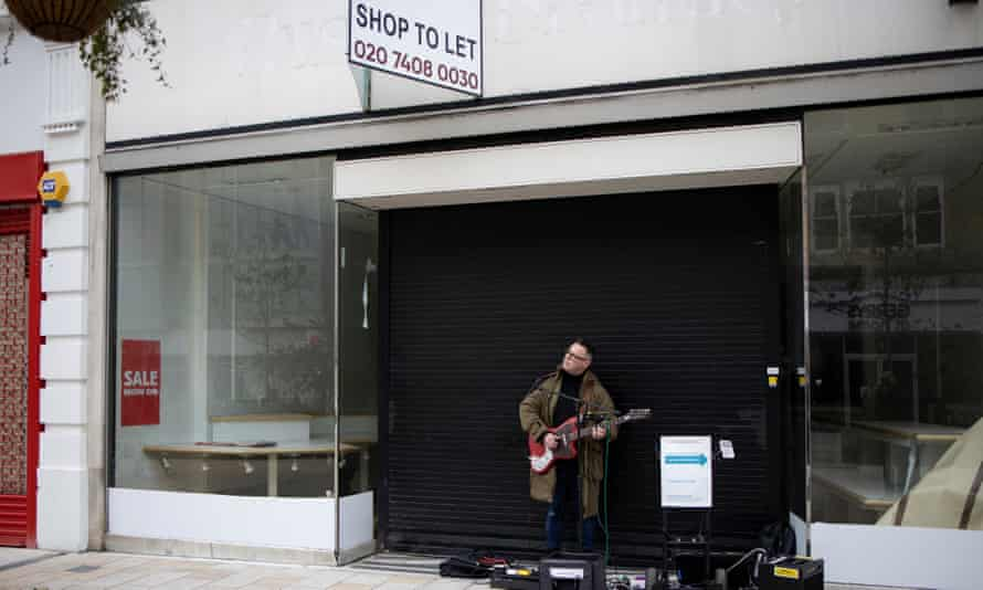 A busker outside a vacant shop on Bromley High Street
