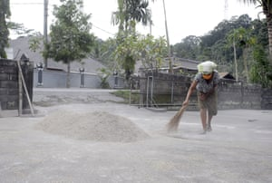 A woman sweeps up the volcanic ash that's fallen in her yard
