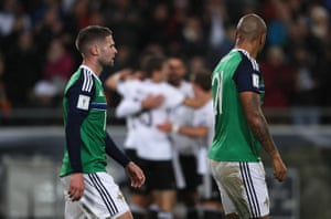 Northern Ireland's Oliver Norwood and Josh Magennis look dejected as the German players celebrate after Sami Khedira scored their second goal.