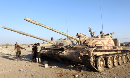 Yemeni pro-government soldiers stand nearby tanks at a position during a ceasefire in the port city of Hodeidah, Yemen