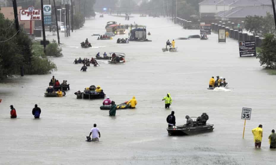 Rescue boats fill a flooded street in Houston as people are evacuated.
