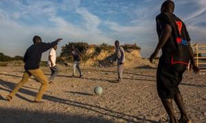 Men playing football in a make shift camp near Calais