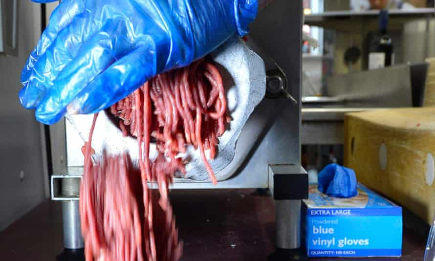 Beef is put through a mincer at a butchers
