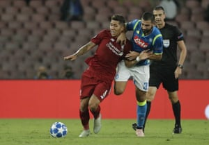 Liverpool's Roberto Firmino is hauled back by Napoli's Raul Albiol .