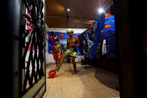 A father plays football with his son in their living room
