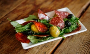 A small plate of salami and salad