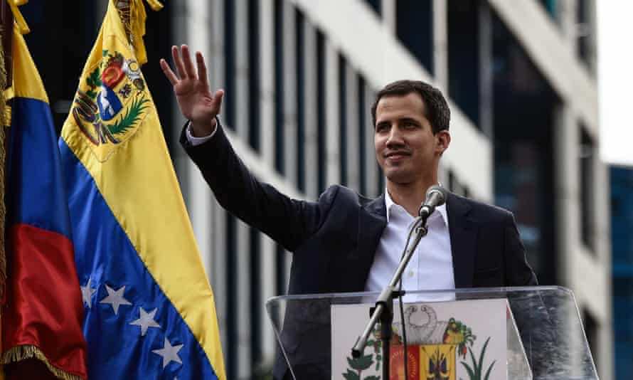 Venezuela's national assembly head, Juan Guaidó, waves to the crowd during a mass opposition rally n which he declared himself the country's 'acting president'.