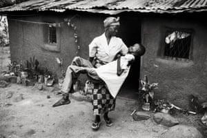 Dorika Gabriel carries her 30-year-old son Joseph to shade, Tanzania,1997.