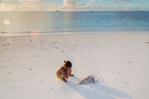 Boy covers face next to dead fish
