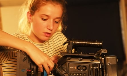 Pupil Bethany Smith changes the lens on a camera during filming