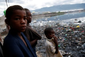 Children stand next to a flooded area in Cité-Soleil, Port-au-Prince.
