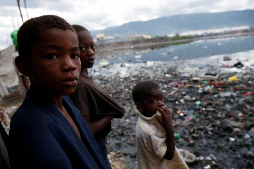 Children stand next to a flooded area in Cité-Soleil, Port-au-Prince.