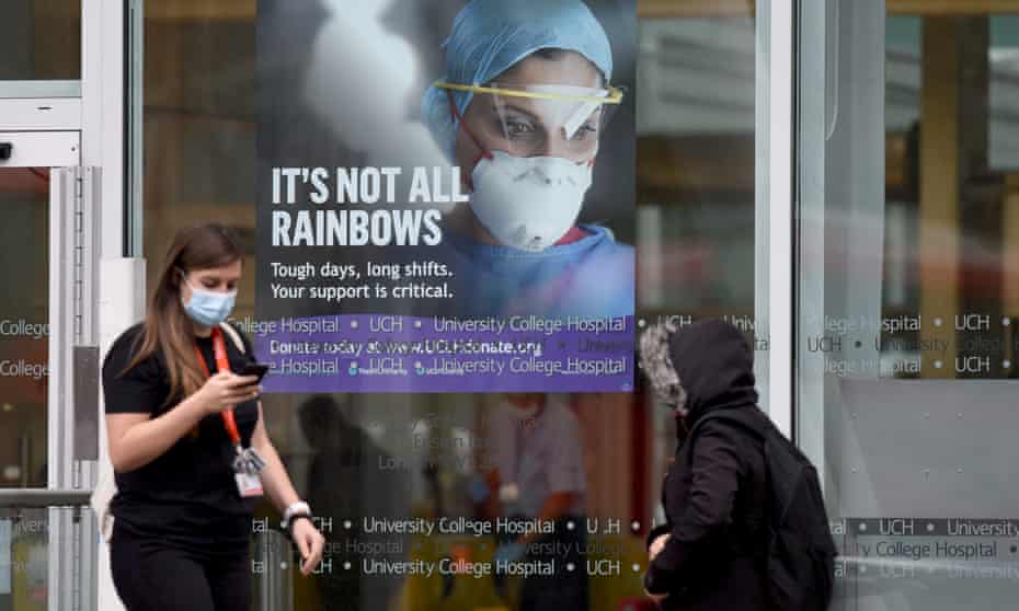 People walking past a coronavirus poster at the University College hospital in central London.