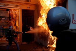 Paris, France: a man tries to extinguish an advertisement hoarding set on fire during a demonstration by union members and workers on another day of strikes against the government's pension reform plans