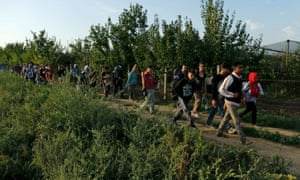A group of refugees walk on the Serbian side of the border near Sid.
