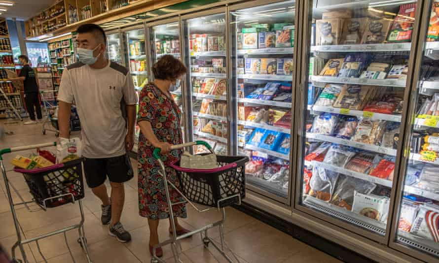 People walk next to frozen food on shelves in a store that focuses on imported goods, in Beijing, China.