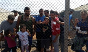 Migrants stand behind a fence at the Dhekelia military base in Cyprus