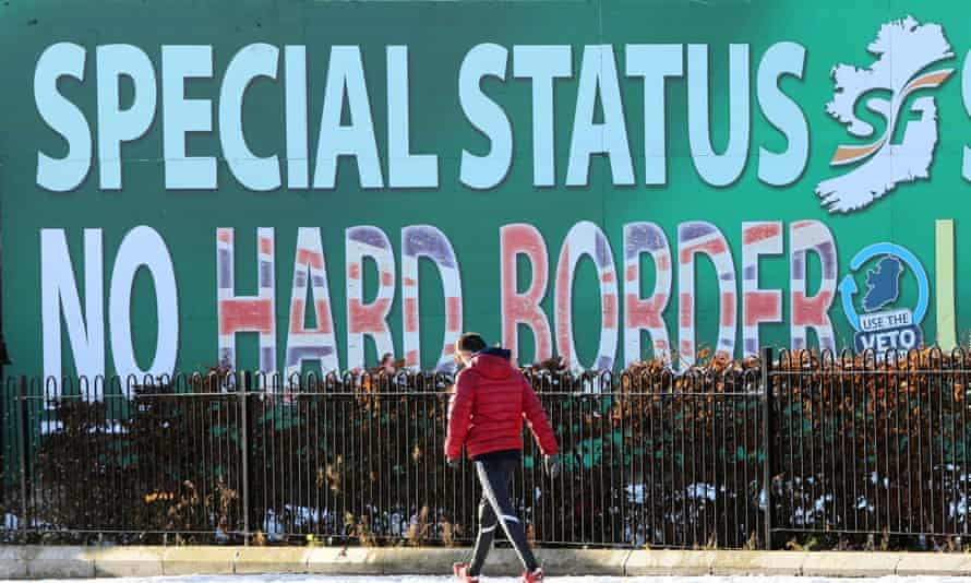 A pedestrian walks past a Sinn Féin billboard in west Belfast that calls for a special status for Northern Ireland.