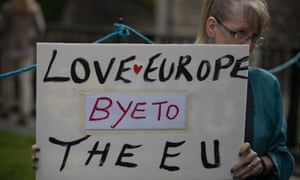 A woman holds up a poster saying farewell to the European Union following Britain's vote to leave.