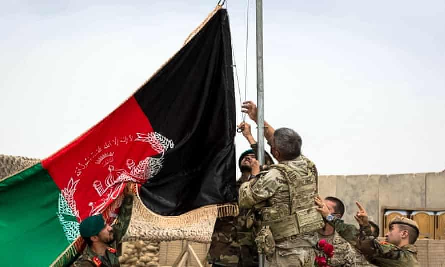 US and Afghan soldiers raise Afghanistan's national flag during a handover ceremony at Antonik camp in Helmand province, Afghanistan, on 2 May.