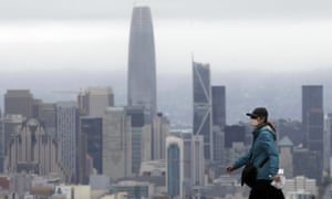 A woman wears a mask during the coronavirus outbreak while walking in front of the San Francisco skyline.