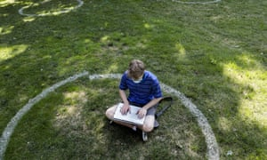 Logan Armstrong, a Cincinnati junior, works while sitting inside a painted circle on the first day of classes at Ohio State University in Columbus, Ohio.