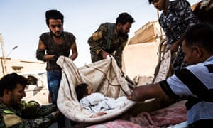 SDF fighters load the dead body of a dead SDF fighter on a truck.