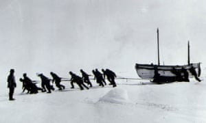The crew of Endurance hauling the lifeboat James Caird, with Shackleton looking on (left).