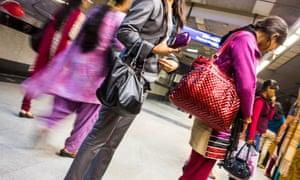 Woman wait for an underground train in Delhi.