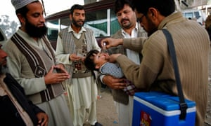 A health worker vaccinates a child against polio in Peshawar City, Pakistan