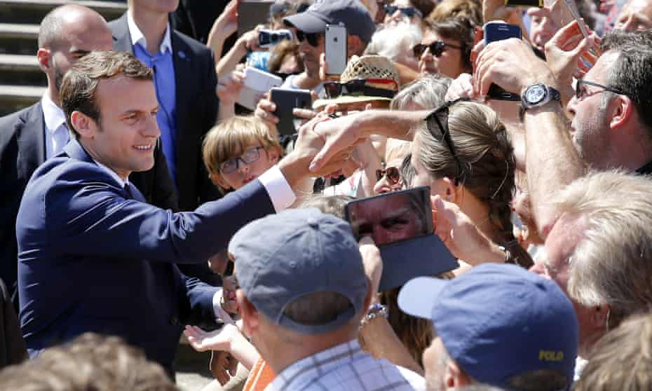 French President Emmanuel Macron shakes hands with the public as he leaves the polling station after casting his vote in the first round of the French elections in Le Touquet-Paris-Plage.