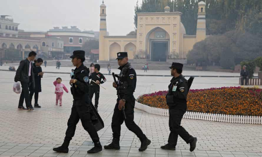 Uighur security personnel patrol near the Id Kah Mosque in Kashgar in western China's Xinjiang region.