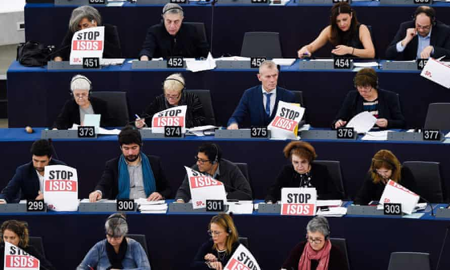 """Members of the European parliament hold panels reading """"Stop ISDS"""" as they take part in a voting session during a plenary session in 13 February 2019 in Strasbourg"""