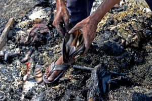 New Delhi, India A Rohingya man looks for his belongings in the charred remains of a refugee camp after a fire