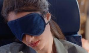 Woman on plane with eye mask