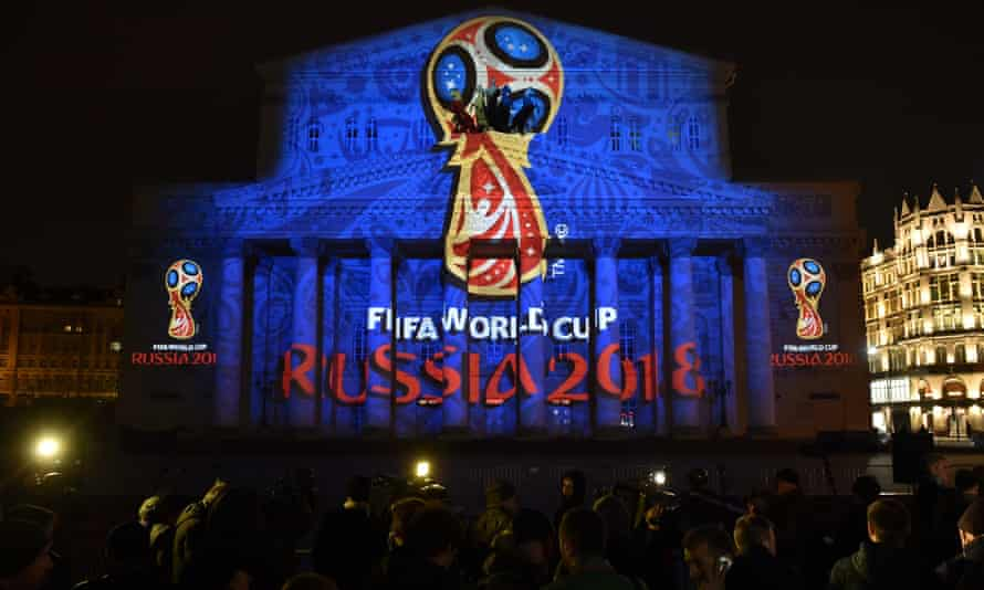 People watch as the facade of the Bolshoi Theatre is illuminated with the official emblem of the 2018 World Cup, which will be held in Russia