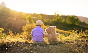 a boy and his teddy in a field